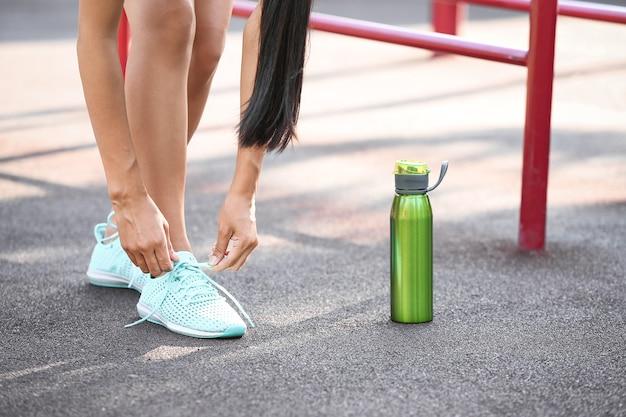 Sportieve jonge vrouw schoenveters buitenshuis binden