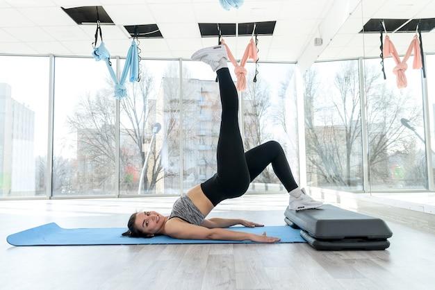 Sportieve jonge vrouw trainen in de sportschool na werkdag. gezonde levensstijl