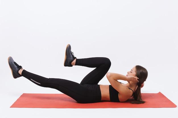 Sportieve jonge vrouwelijke atleet op yogamat die situps over witte achtergrond doet