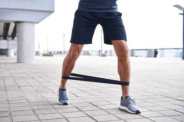 Sportieve jongeman doet oefeningen met rubberen band buiten