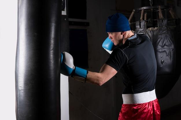 Sportieve jongeman in bokshandschoenen training met bokszak boksen in een sportschool