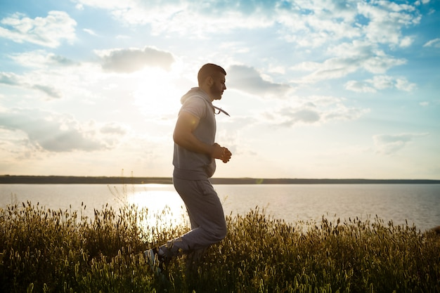 Sportieve jongeman joggen in veld bij zonsopgang.