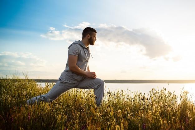 Sportieve jongeman opleiding in veld bij zonsopgang.