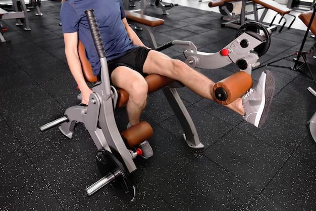 Sportieve jongeman training benen in de sportschool