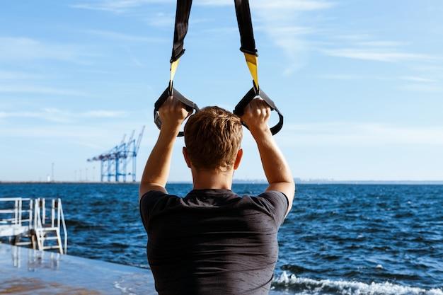 Sportieve jongeman training met trx in de buurt van de zee in de ochtend.