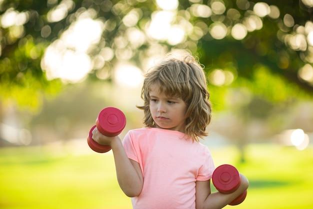 Sportieve jongen met halter buiten. kinderen sporten. jongen die in park uitoefent. actieve, gezonde levensstijl.