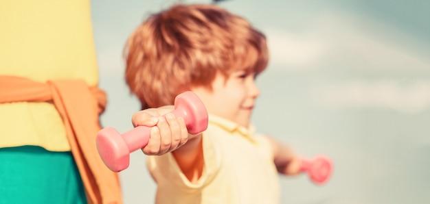 Sportieve jongen met halters. sport. fitness, gezondheid en energie. vrolijke jongen doet oefeningen met halters.