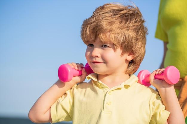 Sportieve jongen met halters. vrolijke jongen doet oefeningen met dumbbell