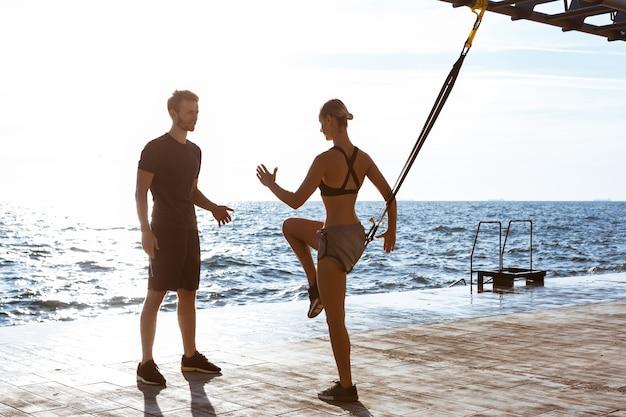 Sportieve jongeren trainen met trx in de buurt van de zee in de ochtend