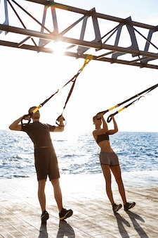 Sportieve jongeren trainen met trx in de buurt van de zee in de ochtend.