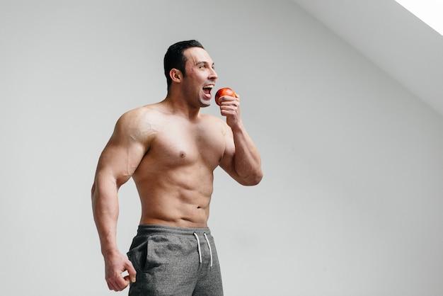 Sportieve kerel die fruit op een witte lijst eet