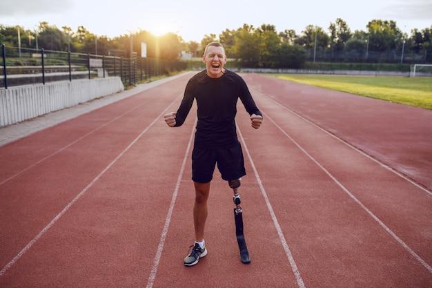 Sportieve knappe kaukasische gehandicapte man met kunstbeen staande op het circuit en zichzelf motiveren om te rennen.