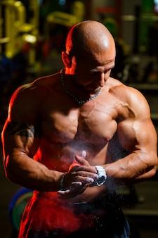 Sportieve knappe sterke man die zich voordeed op de achtergrond van de sportschool. een sterke bodybuilder met perfecte buikspieren, schouders, biceps, triceps en borst.