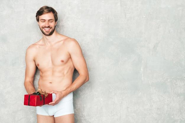 Sportieve knappe sterke man. gezonde atletische fitness model poseren in de buurt van grijze muur in wit ondergoed.