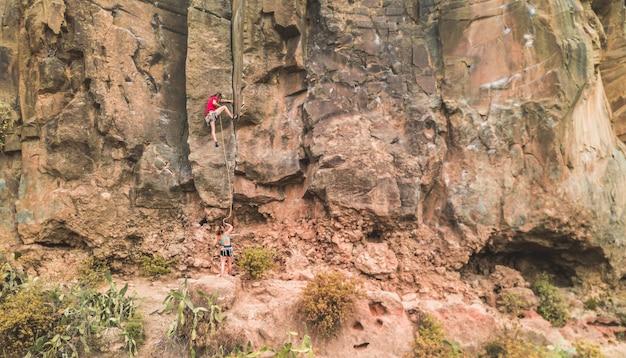 Sportieve man begint een rotswand in een kloof te beklimmen
