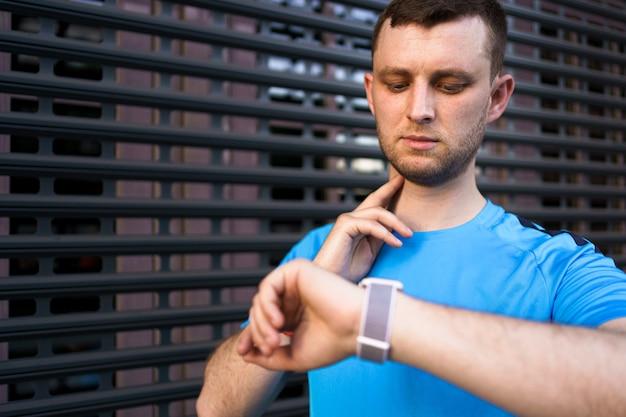 Sportieve man controleert zijn pols tijdens stadstraining