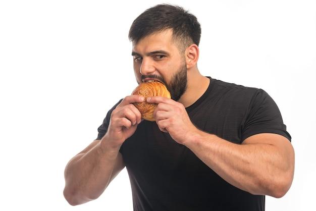 Sportieve man die in zwart overhemd een doughnut eet.