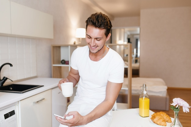 Sportieve man die lacht terwijl hij naar het smartphonescherm kijkt en in de ochtend van thee geniet
