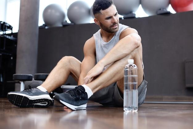 Sportieve man die rust, drinkt water na het sporten.