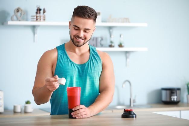 Sportieve man die thuis eiwitshake maakt