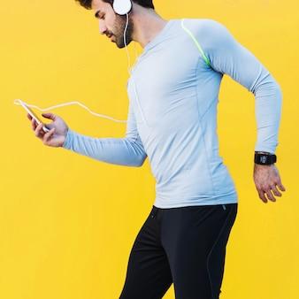 Sportieve man die van muziek op training geniet