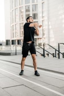 Sportieve man die zijn armen uitstrekt voordat hij gaat joggen. loper in zwarte sportkleding die 's ochtends aan het oefenen is. gezond levensstijlconcept. ochtend stad op de achtergrond. actief leven. buiten fitnessen.