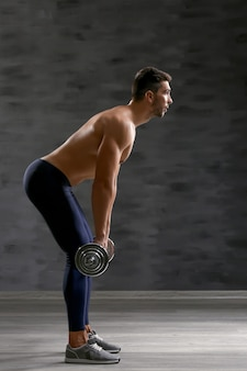 Sportieve man doet oefeningen met barbell binnenshuis