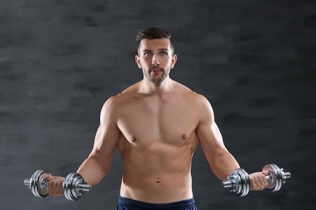 Sportieve man doet oefeningen met halters op donkere achtergrond