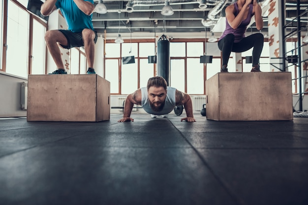 Sportieve man doet push-ups tussen twee atleten.