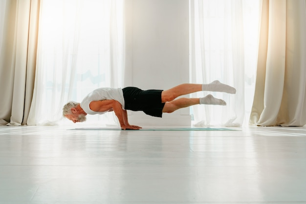 Sportieve man doet thuis yoga-oefening