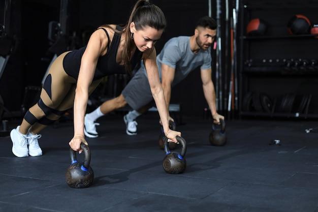 Sportieve man en vrouw doen push-up in een sportschool.
