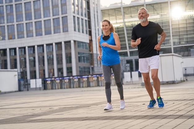Sportieve man en vrouw van middelbare leeftijd in sportkleding die samen buiten joggen met ochtend