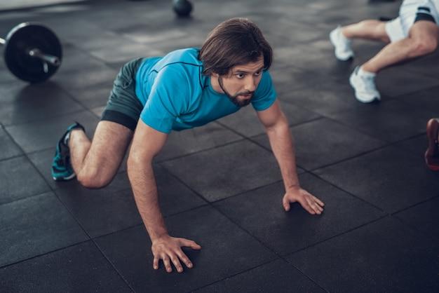 Sportieve man in blauw t-shirt kruipt op gym verdieping.