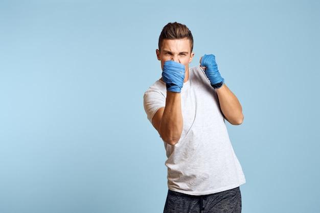 Sportieve man in blauwe bokshandschoenen en t-shirt geïsoleerd