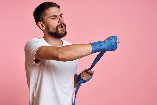 Sportieve man in een wit t-shirt boksbandages op de handen van een roze ruimte van de trainingslevensstijl.