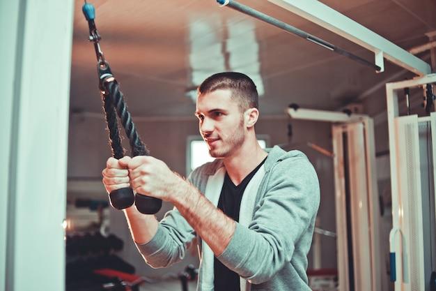 Sportieve man in hoody uitoefening triceps spieren in de sportschool met pull-down touwen fitnessapparatuur machine bijlagen. opleidingsproces.