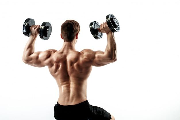 Sportieve man in opleiding oppompen spieren van de rug en handen met halters.