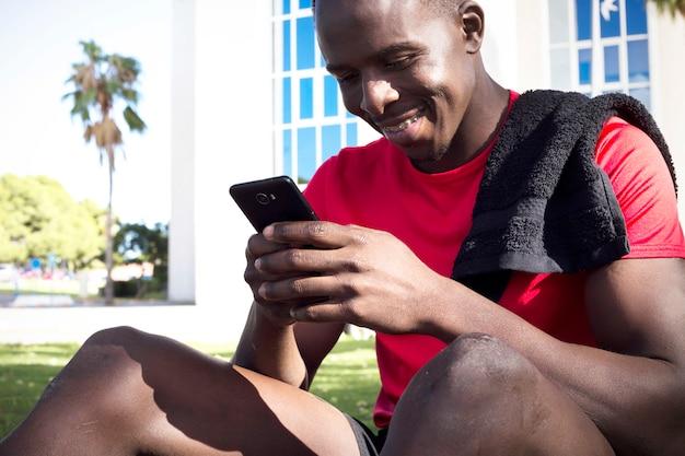Sportieve man in park kijken naar smartphone