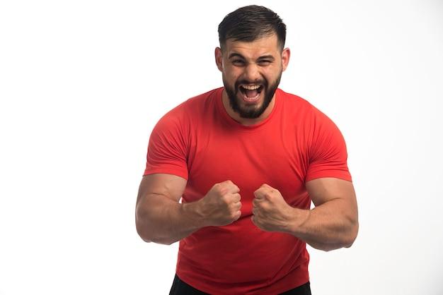 Sportieve man in rood shirt demonstreren zijn armspieren en schreeuwen.