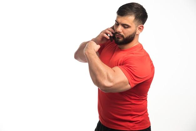 Sportieve man in rood shirt praten aan de telefoon en demonstreren zijn armspieren
