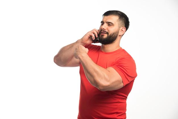 Sportieve man in rood shirt praten aan de telefoon en demonstreren zijn armspieren.