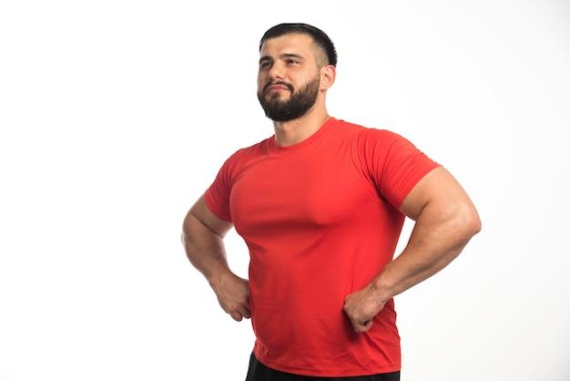 Sportieve man in rood shirt toont zijn armspieren en ziet er zelfverzekerd uit.