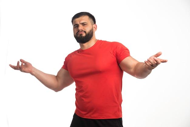Sportieve man in rood shirt ziet er zelfverzekerd uit