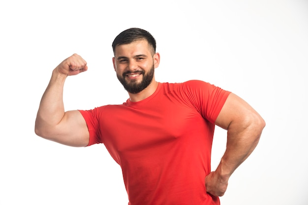 Sportieve man in rood shirt zijn armspieren demonstreren en glimlachen.