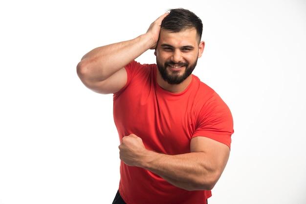 Sportieve man in rood shirt zijn spieren demonstreren.