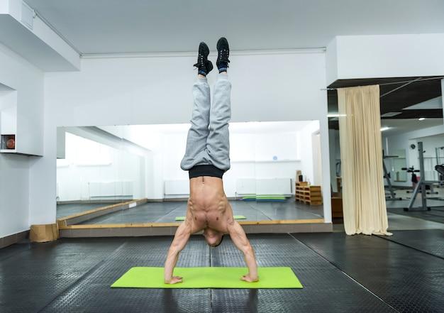 Sportieve man in sportschool staande op handen