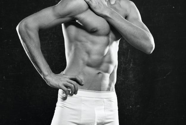 Sportieve man in wit slipje pompte de motivatie voor lichaamstraining op