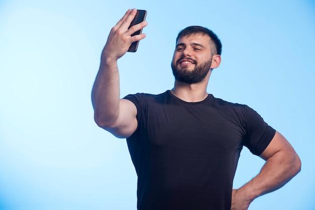 Sportieve man in zwart shirt houdt de telefoon vast en neemt selfie