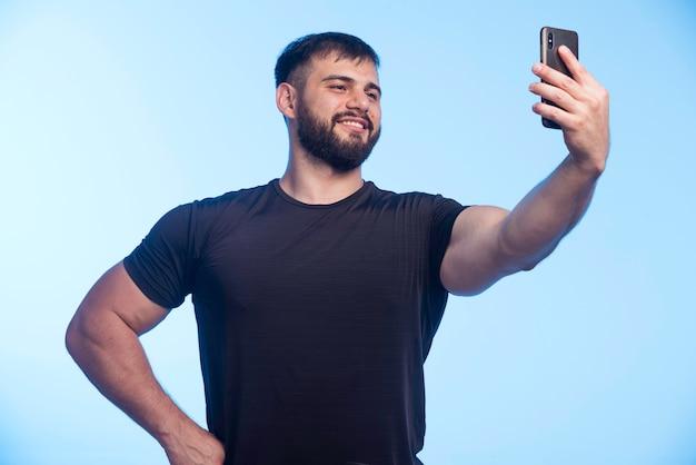 Sportieve man in zwart shirt houdt de telefoon vast en neemt selfie.