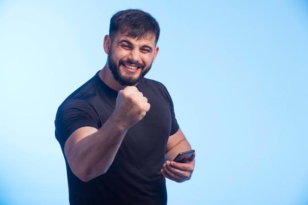 Sportieve man in zwart shirt houdt de telefoon vast en toont vuist